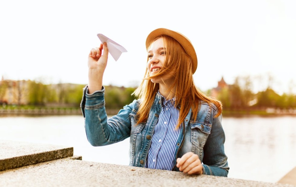 a woman flying a paper airplane