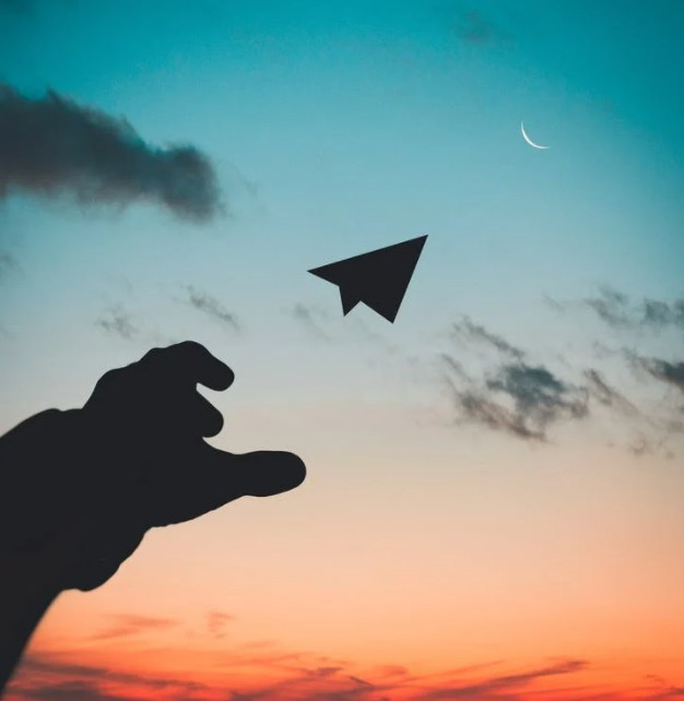 silhouette-photo-of-man-throw-paper-plane