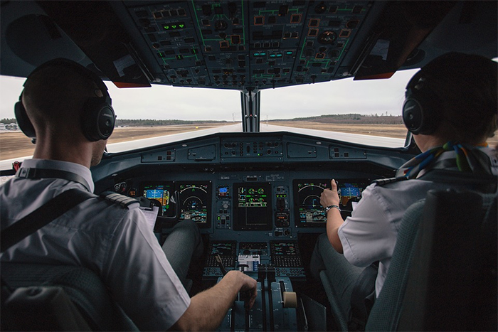 pilots controlling the plane in the cockpit